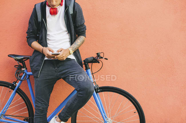 Teenager with a fixie bike, using smartphone leaning on wall — Stock Photo