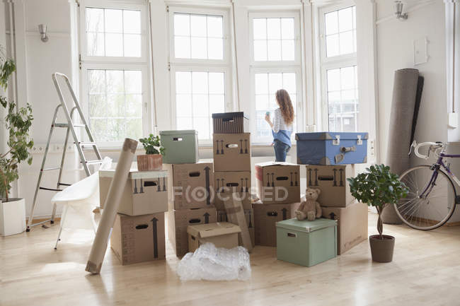 Woman with cardboard boxes in new apartment looking out of window — Stock Photo