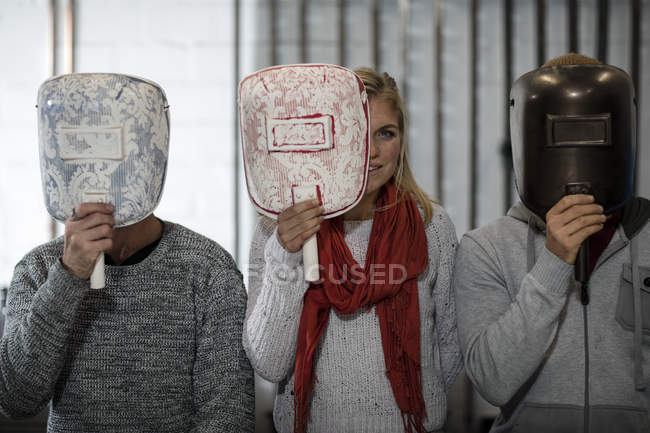 Three people hiding behind designer masks — Stock Photo