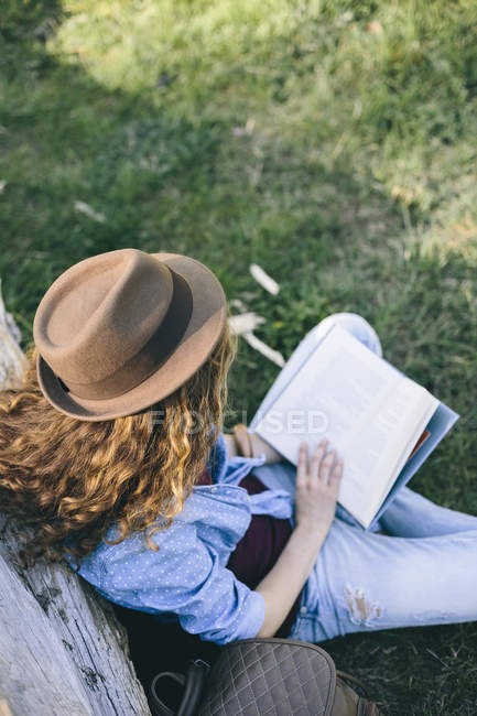 Frau sitzt auf einer Wiese, ein Buch zu lesen — Stockfoto