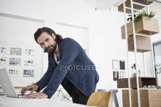 Homme utilisant un ordinateur portable dans le bureau regardant la caméra — Photo de stock