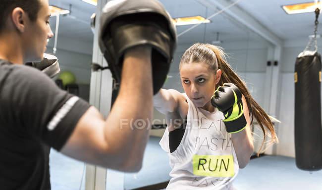 Молодая женщина в спортзале занимается боксом — стоковое фото