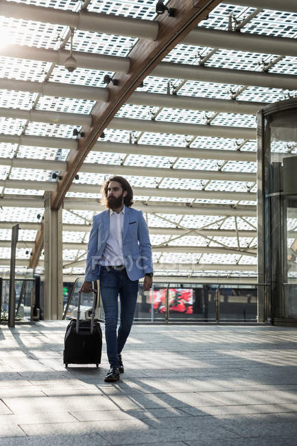 Businessman walking with suitcase — Stock Photo