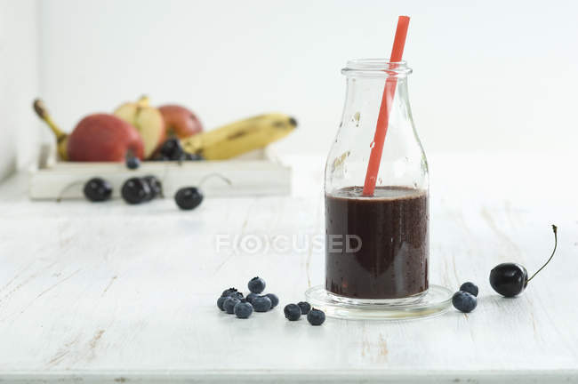 Blueberry Smoothie in bottle with straw — Stock Photo