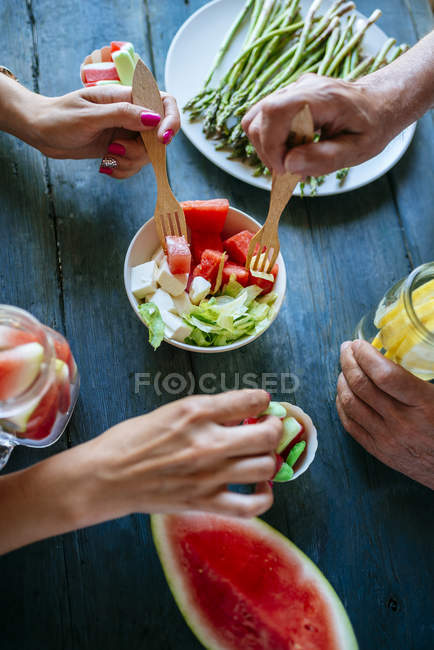 Male and female hands eating salad, watermelon, lemonade, asparagus and candy on wooden table — Stock Photo