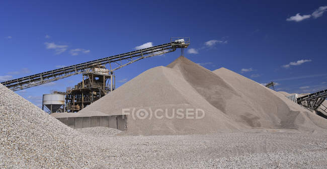 Conveyor belt pouring sand on heap — Stock Photo