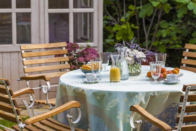 Cobertizo de jardín y mesa puesta en el jardín - foto de stock