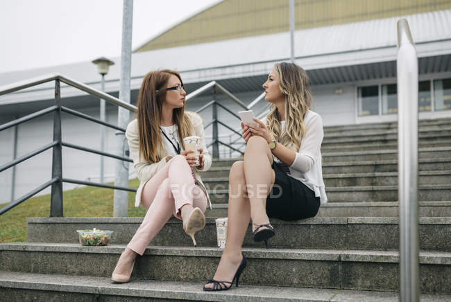 Two women having coffee break outdoors — Stock Photo