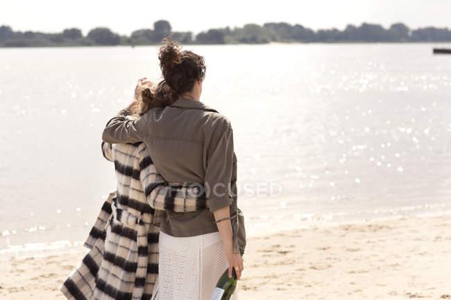 Вид сзади на двух друзей, идущих рука об руку на пляже с бутылкой игристого вина — стоковое фото
