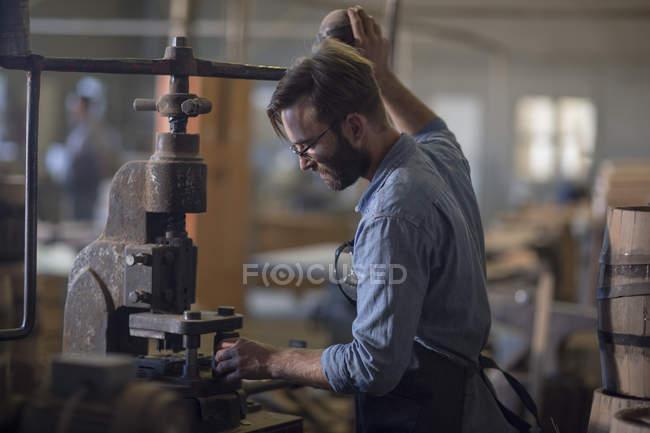 Кочегар, работающий на старой машине в мастерской — стоковое фото