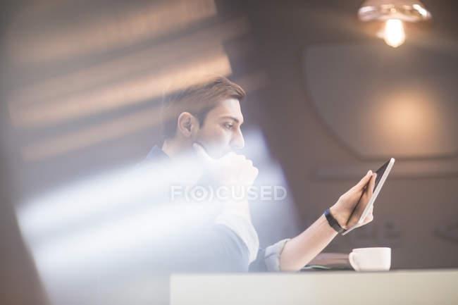 Homme avec tablette numérique au bureau de réflexion — Photo de stock
