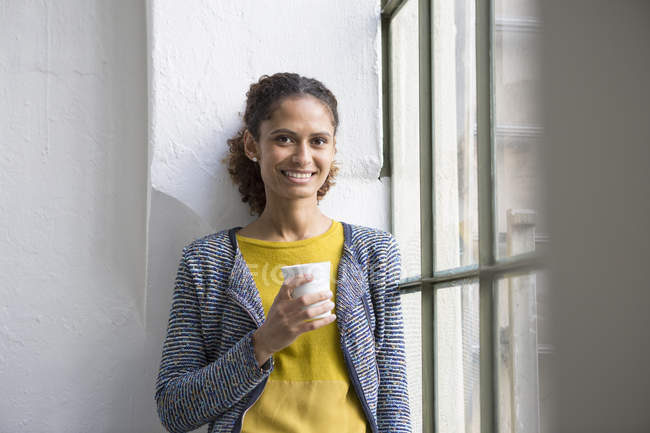 Young woman standing at the window with a cup of coffee — Stock Photo