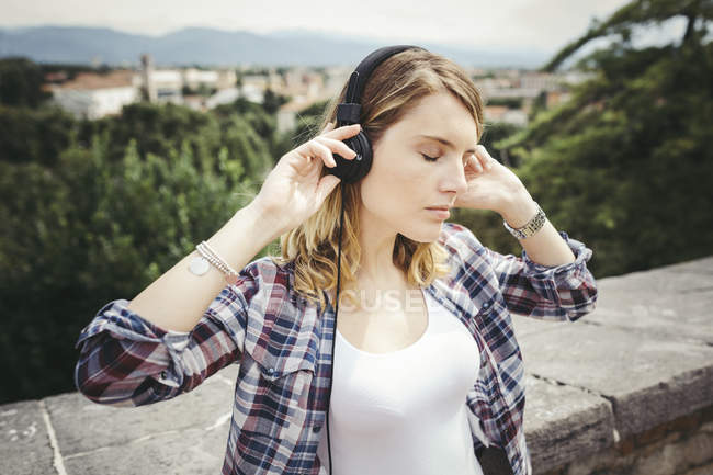 Young woman listening music with headphones — Stock Photo