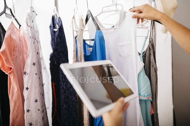 Mulher com tablet digital no guarda-roupa — Fotografia de Stock