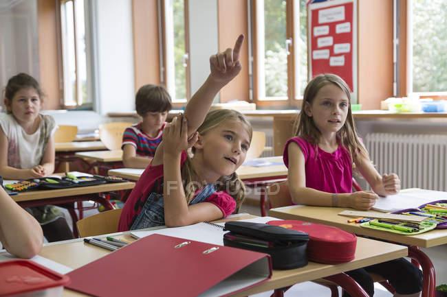 Scolara che solleva la sua mano in classe a scuola — Foto stock