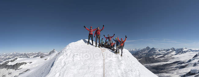 Italy, Gressoney, Alps, Castor, group of mountaineers standing on mountain peak — Stock Photo