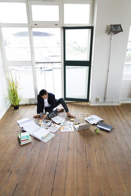 Hombre de negocios trabajando descalzo en piso - foto de stock