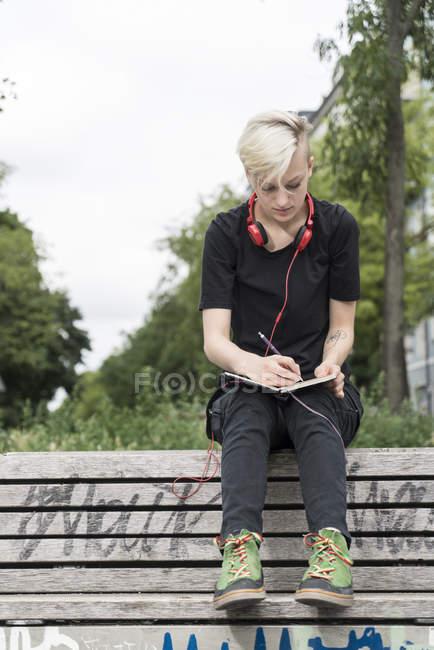 Junge Frau zeichnet auf Parkbank — Stockfoto