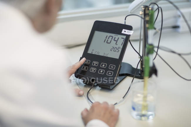 Cropped image of person working in lab checking measurements — Stock Photo
