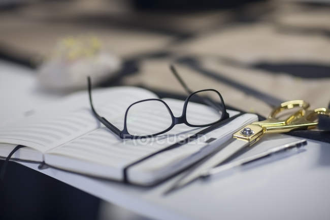 Scissors, glasses and notebook on table — Stock Photo