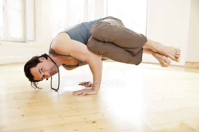 Man in sunny yoga studio holding Parsva Bakasana pose — Stock Photo