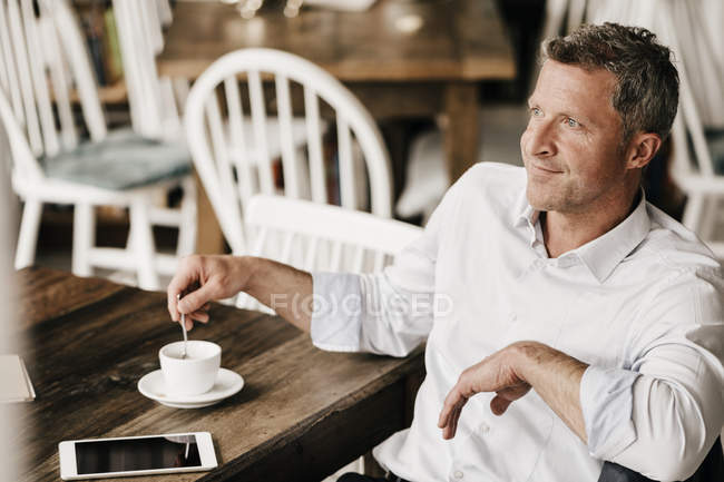 Businessman in cafe drinking coffee — Stock Photo