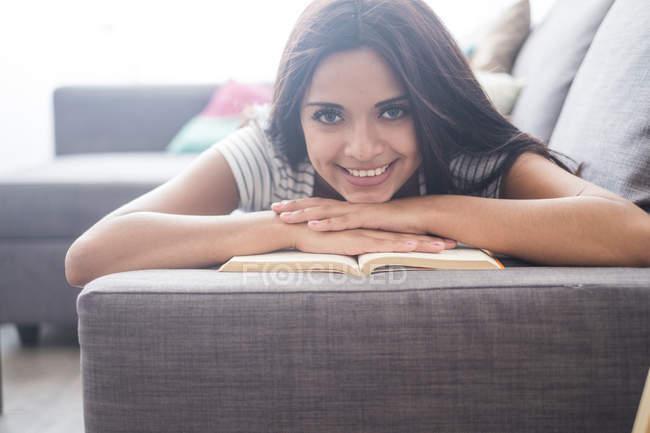 Ritratto di adolescente sorridente sdraiata sul divano con un libro — Foto stock