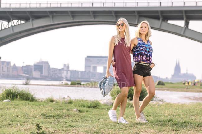 Women walking at riverbank — Stock Photo