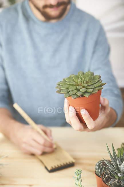 Homme tenant plante succulente et prendre des notes — Photo de stock