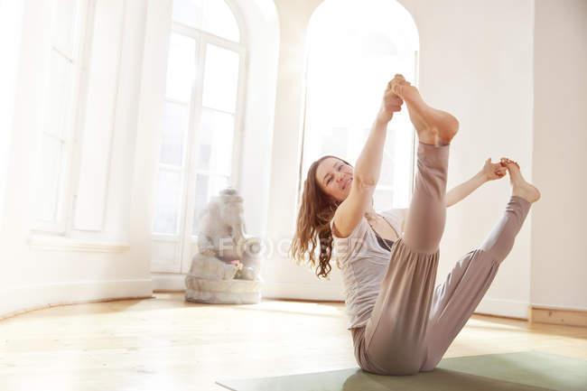 Frau im sonnigen Yogastudio hält eine erweiterte Navasana-pose — Stockfoto