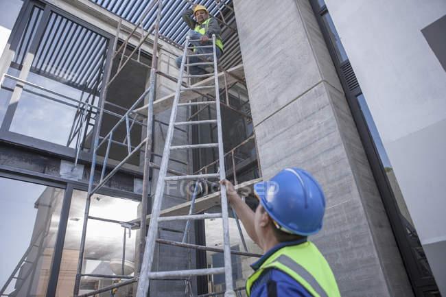 Due operai edili su ponteggi che lavorano in cantiere — Foto stock