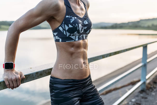 Woman leaning on railing showing abdominal muscles — Stock Photo