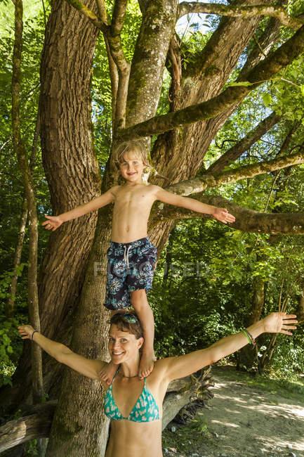 Kleiner Junge balanciert auf den Schultern seiner Mutter — Stockfoto