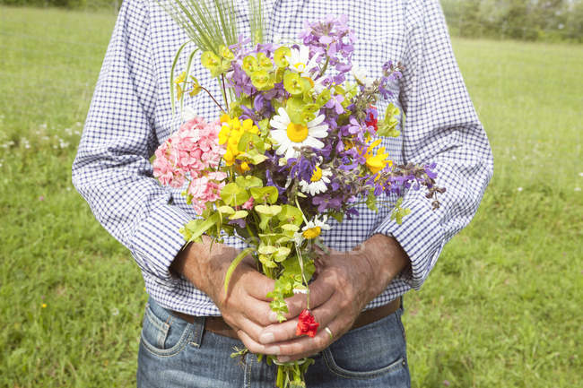 Man holding bunch of flowers — Stock Photo