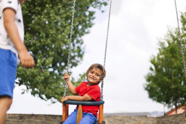Portrait of happy little boy sitting on a swing — Stock Photo