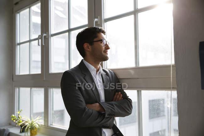 Empresário na janela de pé com os braços cruzados — Fotografia de Stock