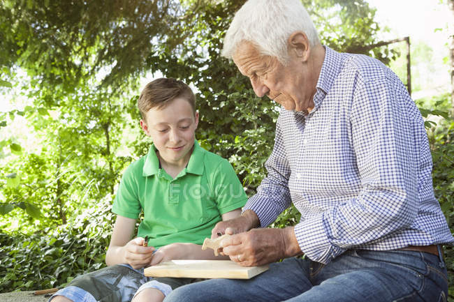 Grandfather and grandson carving wood together — Stock Photo