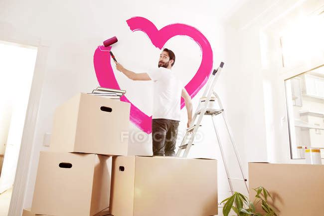 Young man painting pink heart on wall in new apartment — Stock Photo