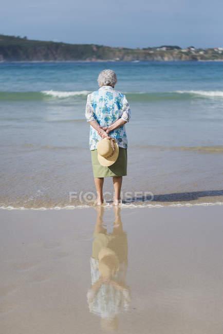 Senior woman standing on beach — Stock Photo