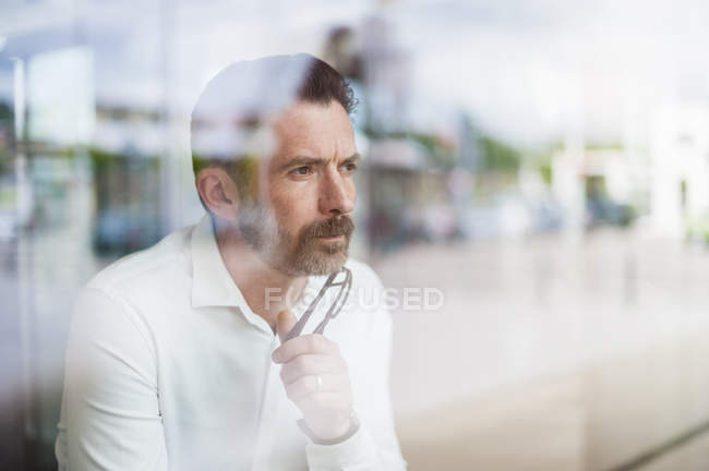 Businessman looking through window — Stock Photo