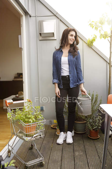 Smiling young woman with potted plant — Stock Photo