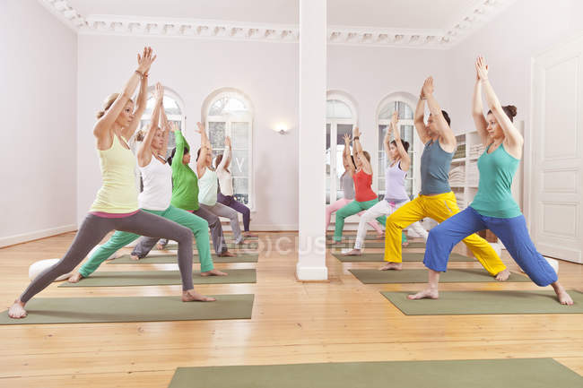 Group of people in yoga studio holding Virabhadrasana pose — Stock Photo