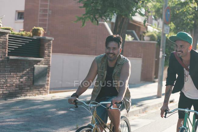 Due uomini sorridenti in bicicletta per strada in città nella giornata di sole — Foto stock
