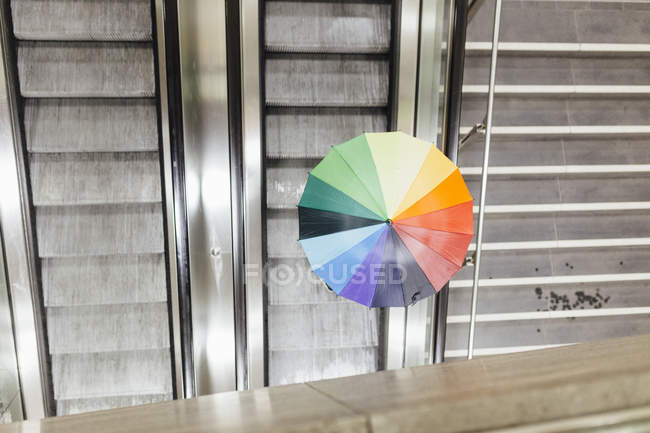 Person with colorful umbrella standing on escalator — Stock Photo