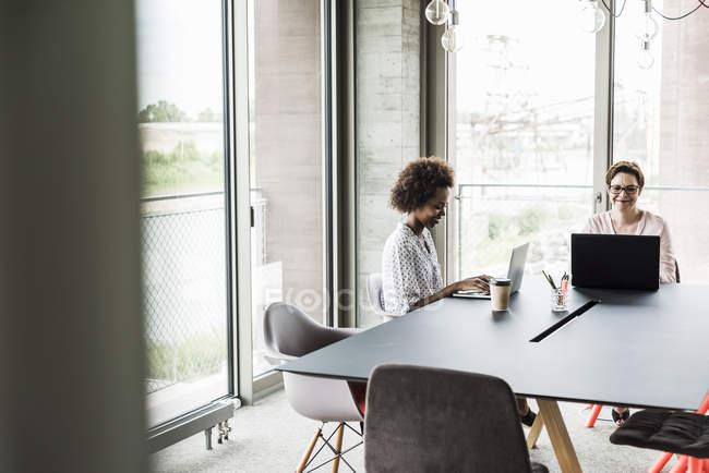 Mujeres que trabajan en oficina moderna - foto de stock