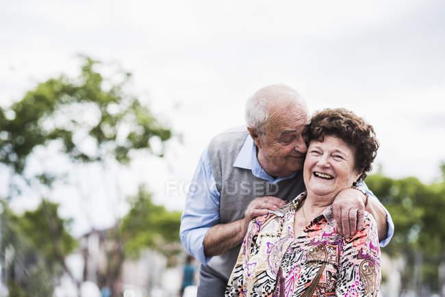 Старшая пара обнимается на улице — стоковое фото