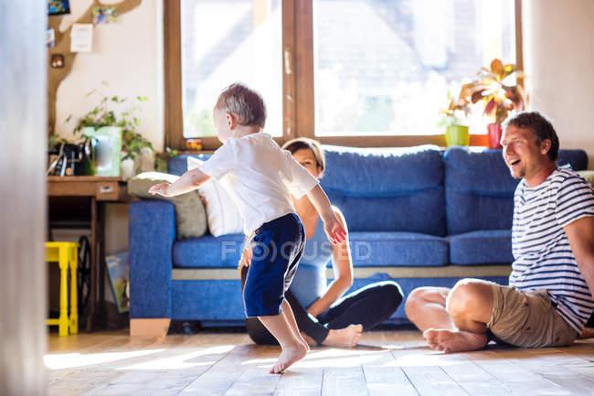 Padre e madre incinta che giocano con il figlio a casa — Foto stock