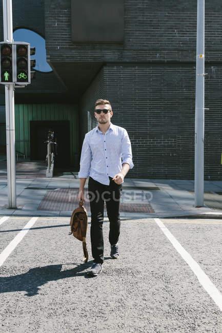 Businessman crossing street — Stock Photo