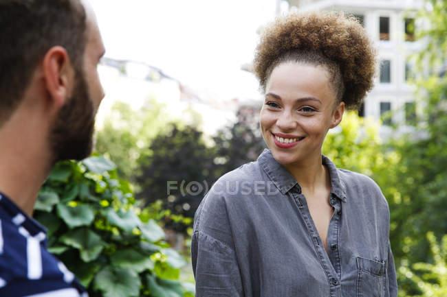 Молода жінка, Усміхаючись на людину в парку — стокове фото