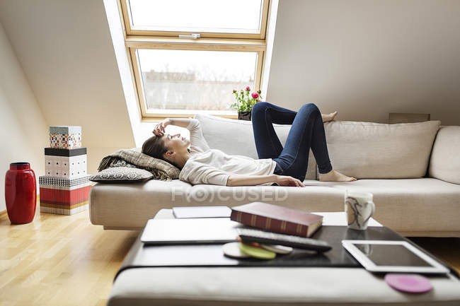 Relaxed woman lying on couch — Stock Photo